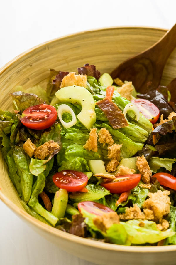 Adding croutons and other more delicate add-ins to the tossed salad recipe and serving.