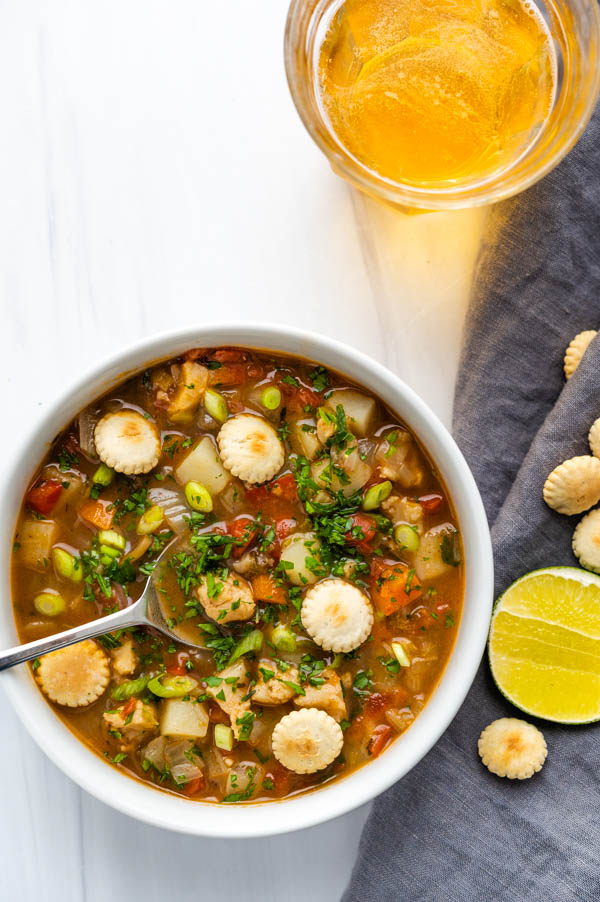 Serving a bowl of conch chowder with oyster crackers, lime and a beer.