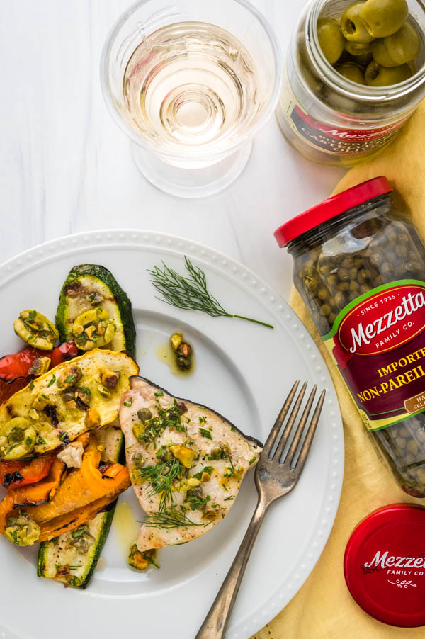 a dinner plate with grilled swordfish steak, zucchini, squash and olive relish spooned over the top.