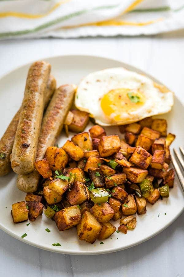 Serving breakfast fries with eggs and sausage.