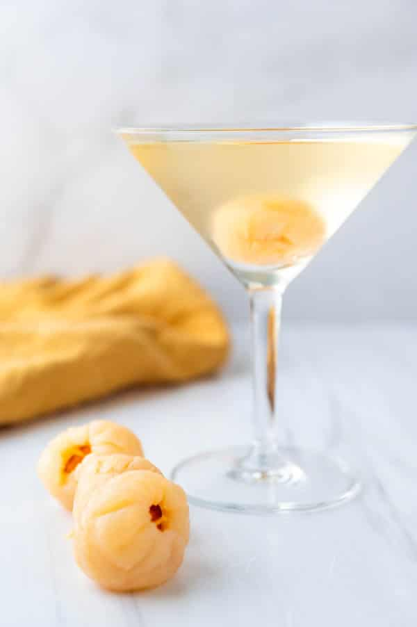 Serving lychee cocktail with lychee garnish.