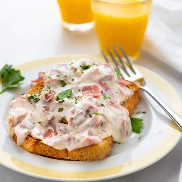 A serving of creamed chipped beef on toast with a fork and orange juice.