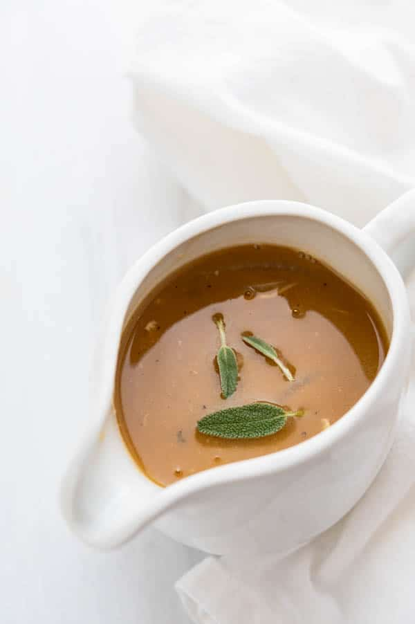 a bowl of gravy with sage leaves for the marinated turkey breast.