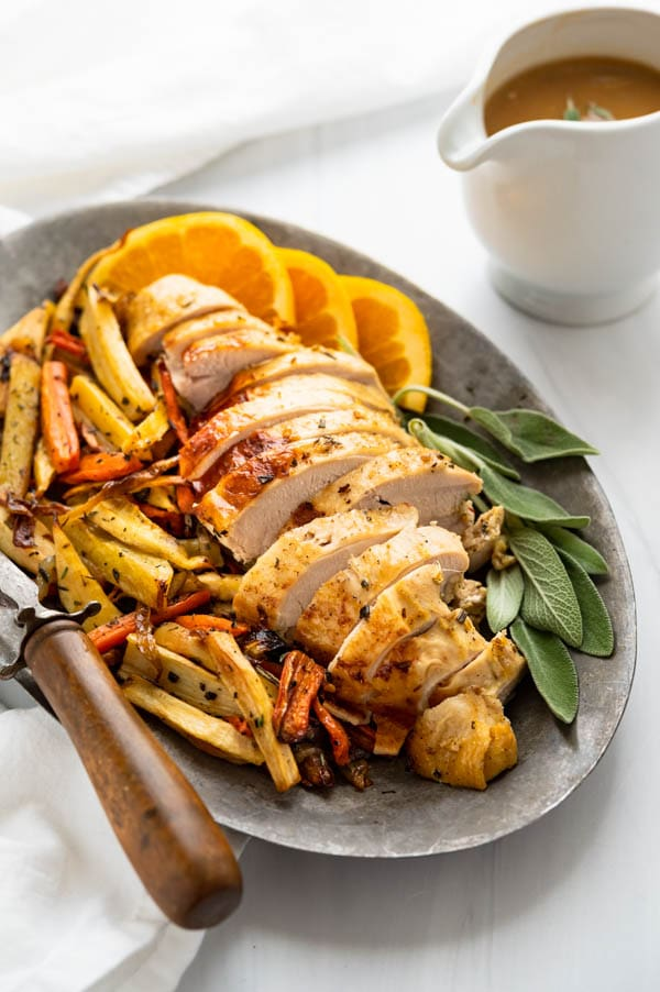 Sliced turkey breast on a platter with save and roasted veggies.