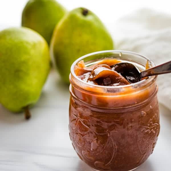 a jar of pear butter with a spoon.