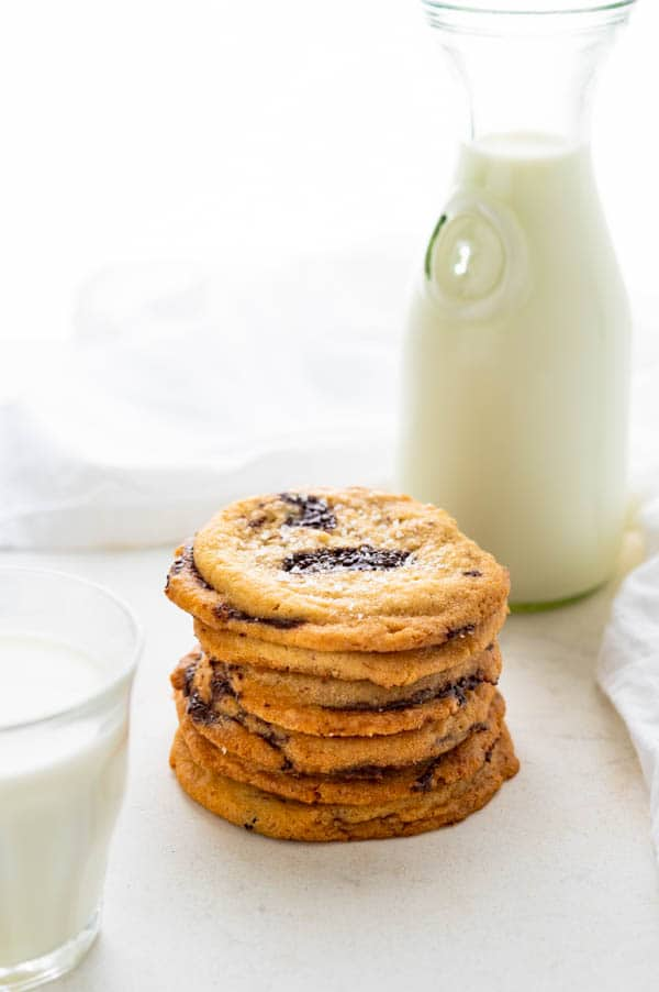 a stack of tahini cookies with a glass of milk.