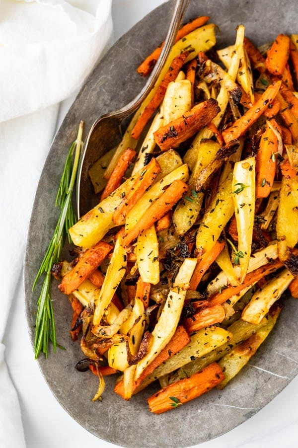 Serving roasted carrots and parsnips on a pewter platter.