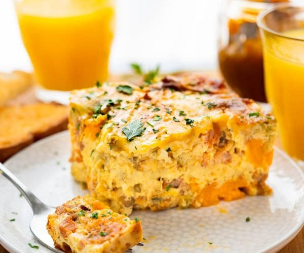 Chorizo Egg Bake on a plate with orange juice and other breakfast fixings.