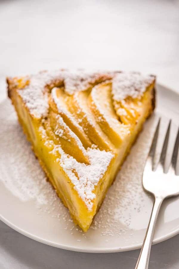 a slice of apple almond tart on a plate.