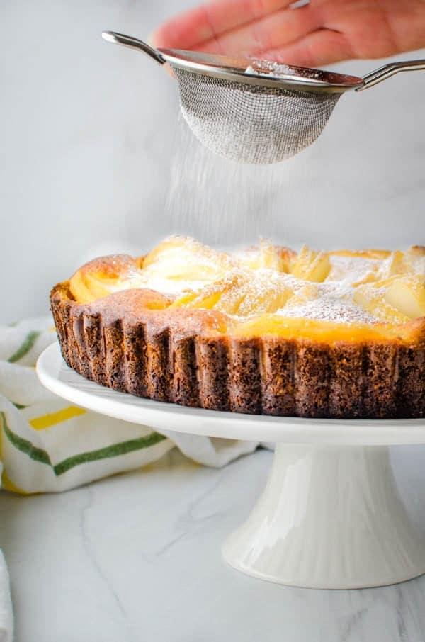 garnishing the tart with powdered sugar.