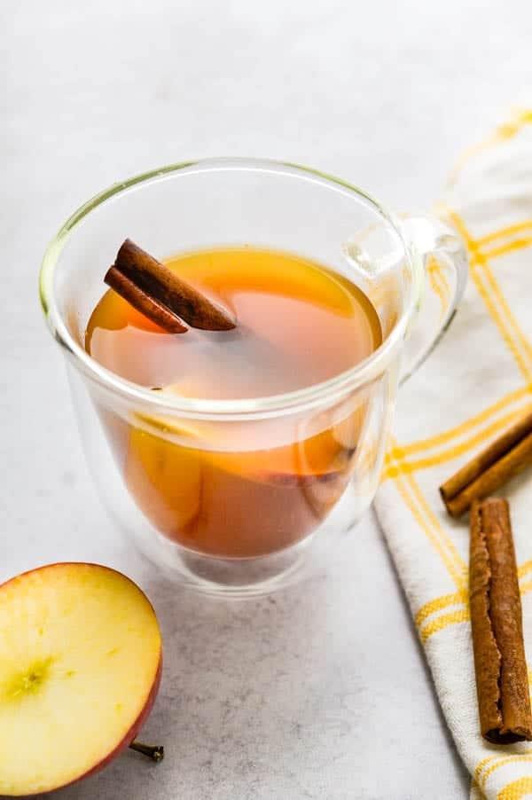 Serving apple flavored green tea with a cinnamon stick and slice of apple.