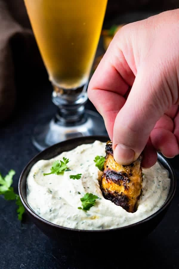 Dipping Grilled Wings into Hatch Chile chicken wing dipping sauce.