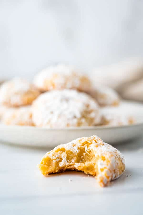 taking a bite of the gluten free almond cookies to show the interior texture.
