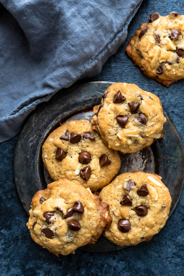 a dull silver plate with a pile of almond chocolate chip cookies.