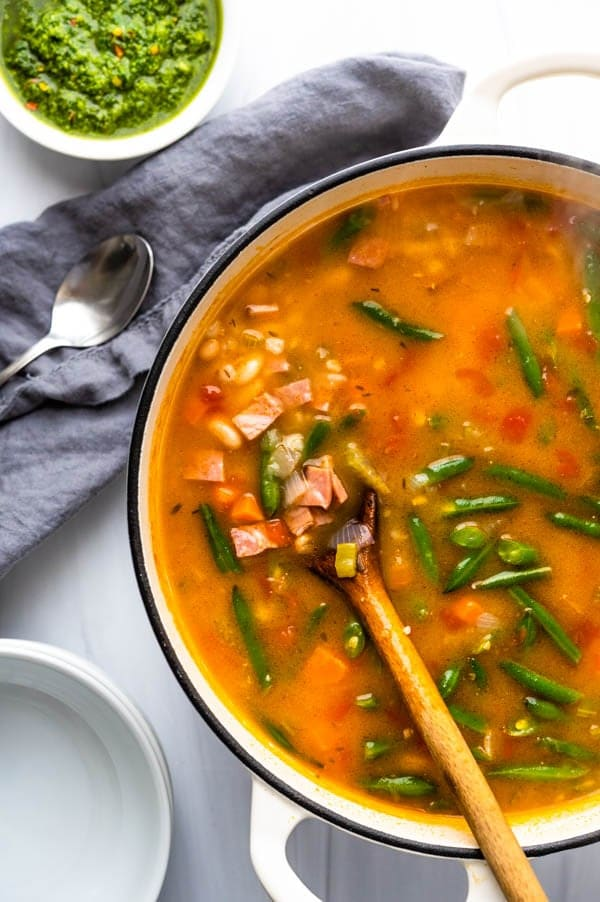 Serving ham vegetable barley soup with pistou from a dutch oven.
