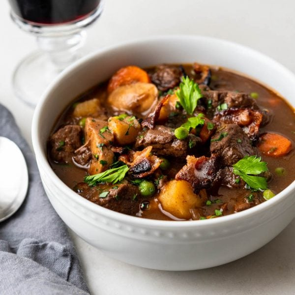 a bowl of beef stew with a glass of wine.