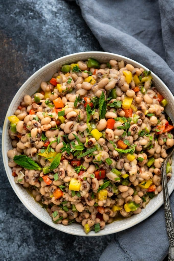 a bowl of black eyed pea salad with a spoon.