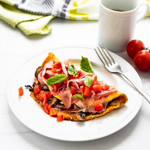 tomato mushroom omelette on a plate with fresh basil.
