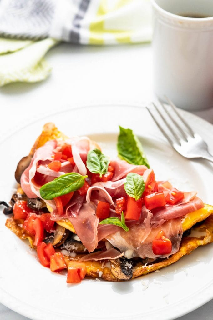 finishing the Italian omelette with prosciutto ham, tomato and fresh basil.