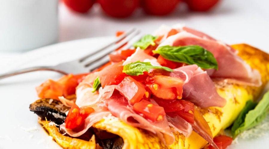Closeup photo of Italian mushroom tomato and prosciutto omelette with cheese.