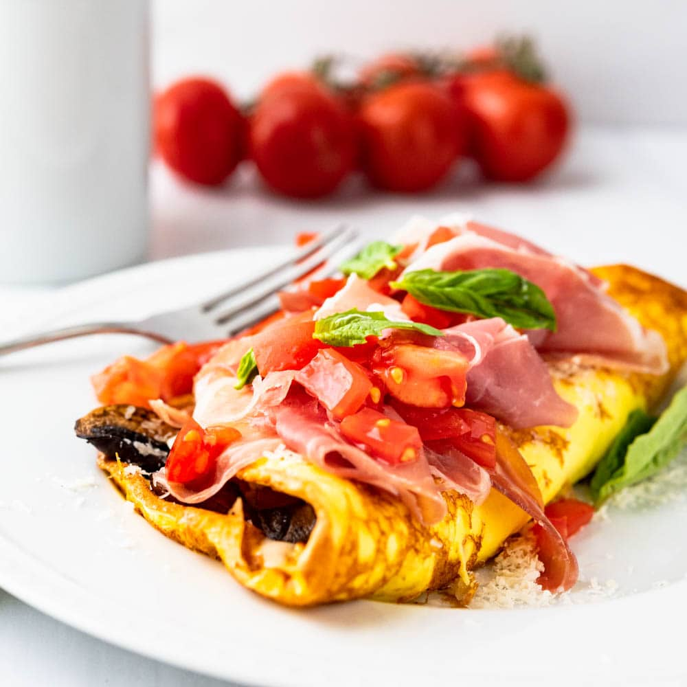 Closeup photo of Italian mushroom tomato and prosciutto omelette with cheese.