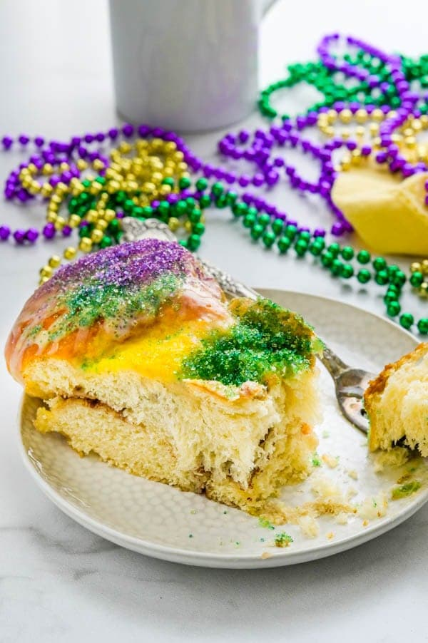 A slice of traditional King cake with Mardi Gras beads.
