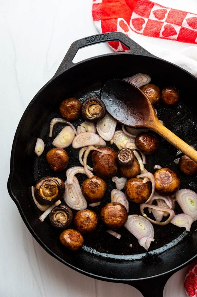 cooking mushrooms and shallots in a cast iron pan.
