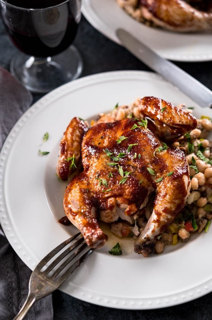 A plate with beans and a whole roasted young chicken.