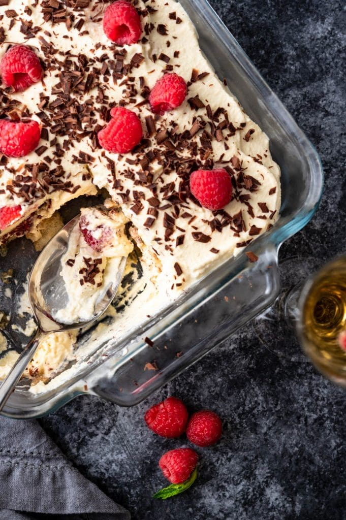 Finished Italian tiramisu with a scoop missing from the dish.