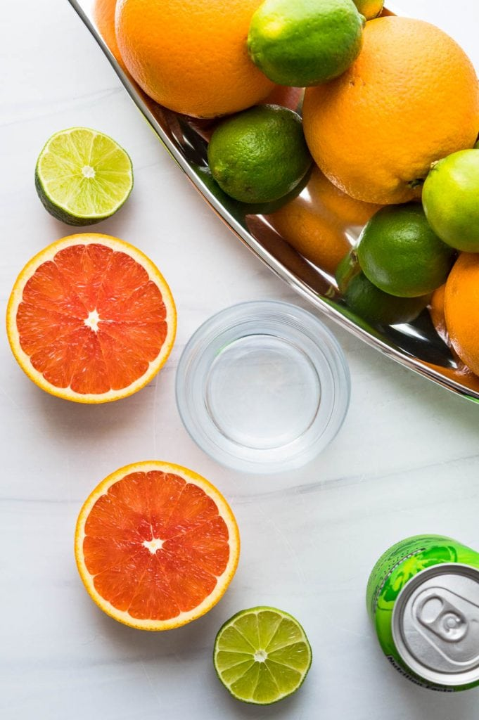 an overhead shot of sliced oranges and limes with sparkling water for a non alcoholic margarita.