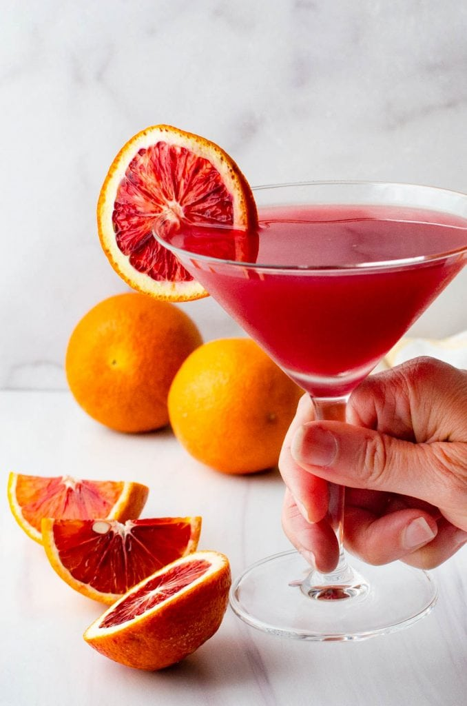 Garnishing a blood orange martini with a slice of orange.