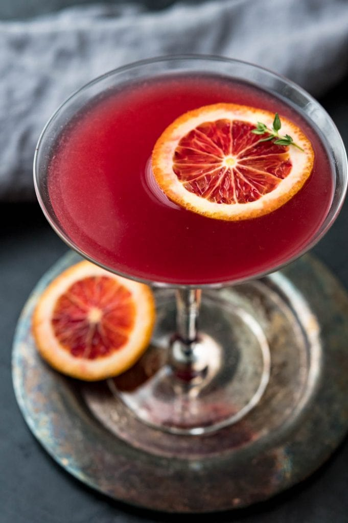 a moody image of the red cocktail with a slice of blood orange and sprig of thyme.