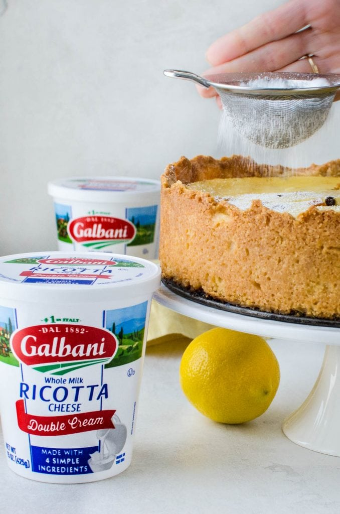sprinkling sugar on the easter pie with a container of Galbani ricotta next to it.