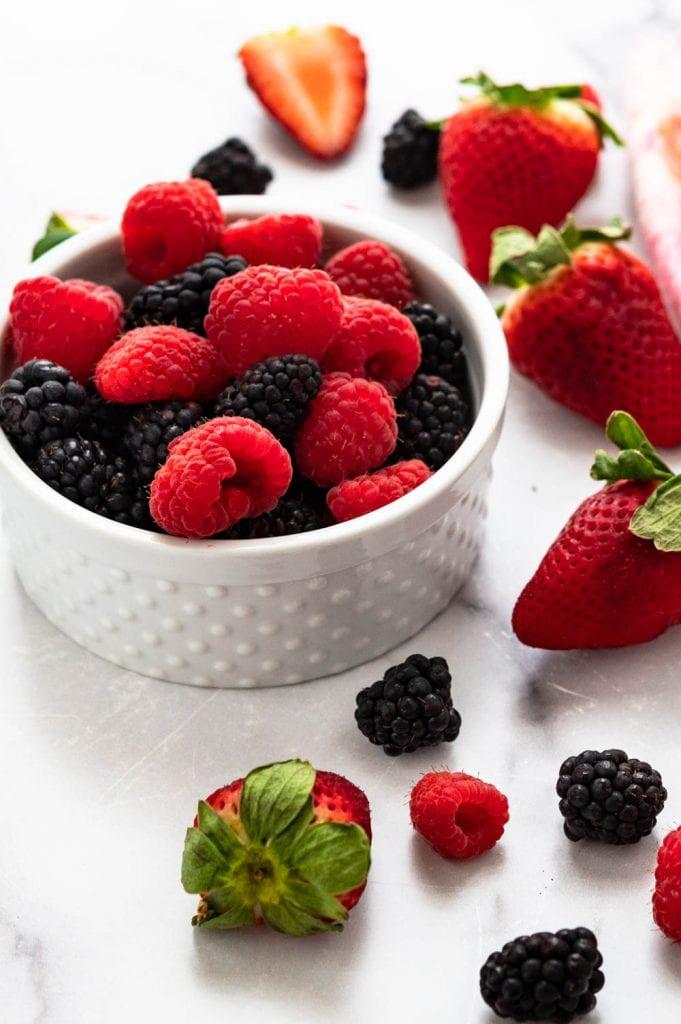 a bowl of raspberries, blackberries and strawberries.