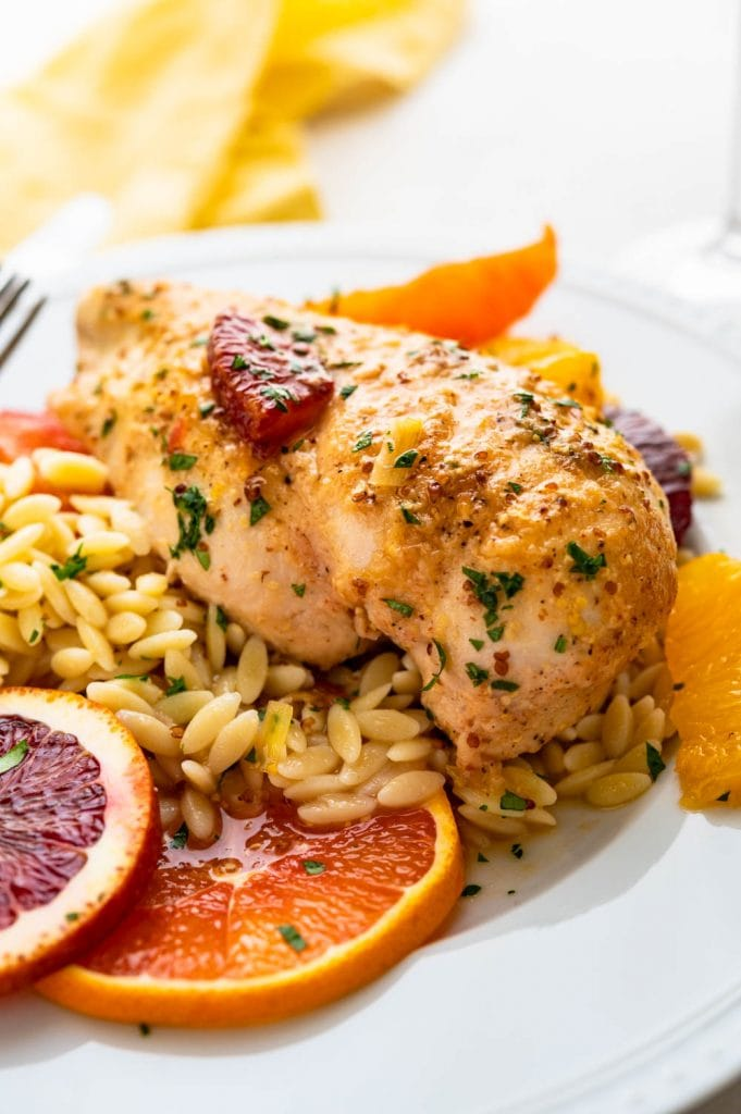 serving orange chicken over a bed of orzo.