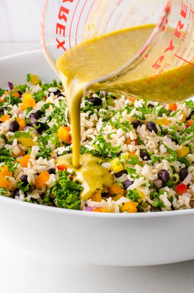 adding cumin lime dressing to the black bean and rice salad.