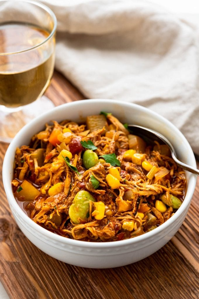 A bowl of chicken brunswick stew in a bowl with a glass of wine.