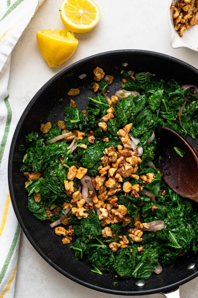 adding walnuts to blanched kale.