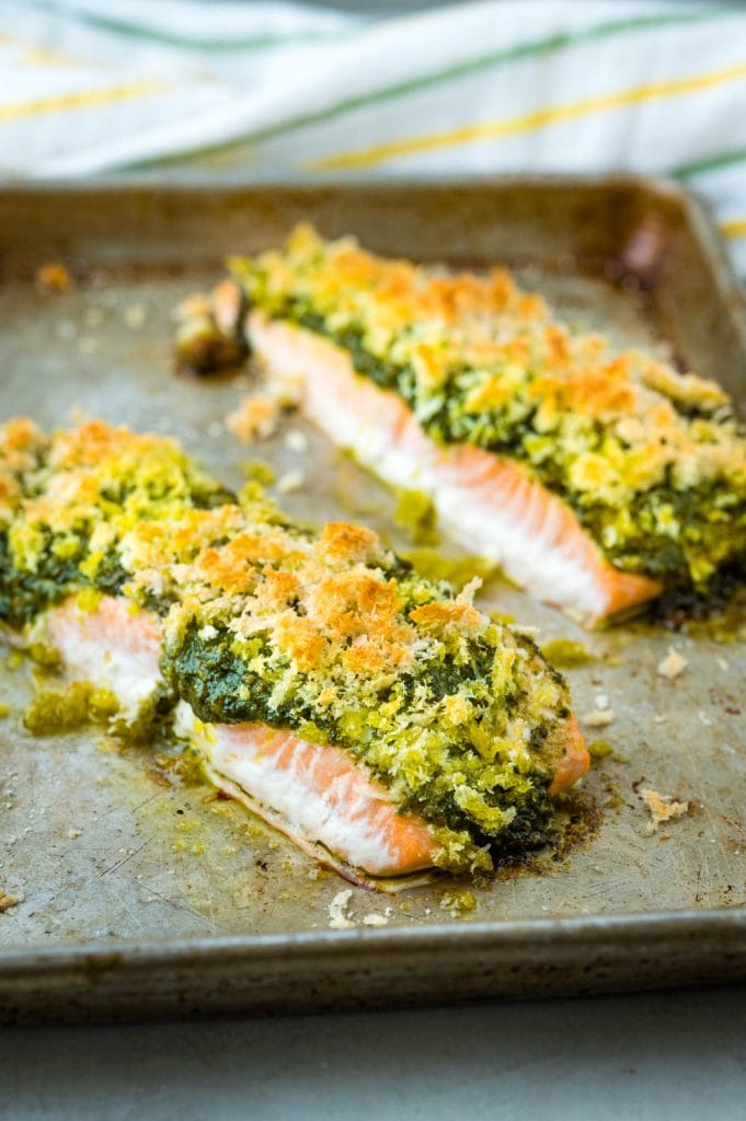 The golden crust and pesto sauce on the baked salmon fillets.