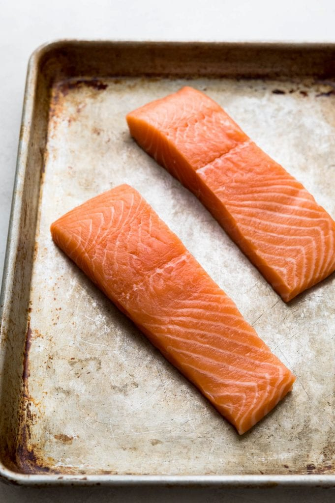salmon fillets on a baking sheet.