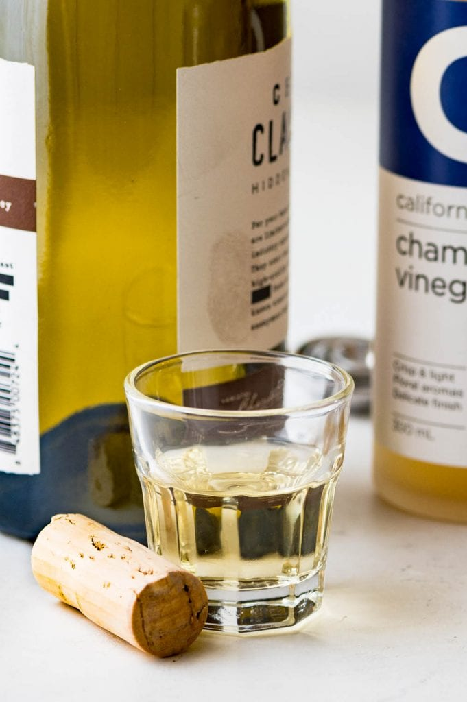 white wine in a small glass with a cork.