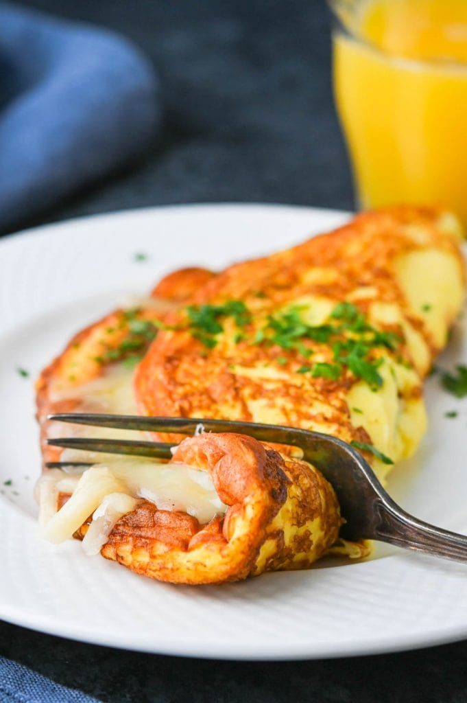 cutting into the cheese omelette.