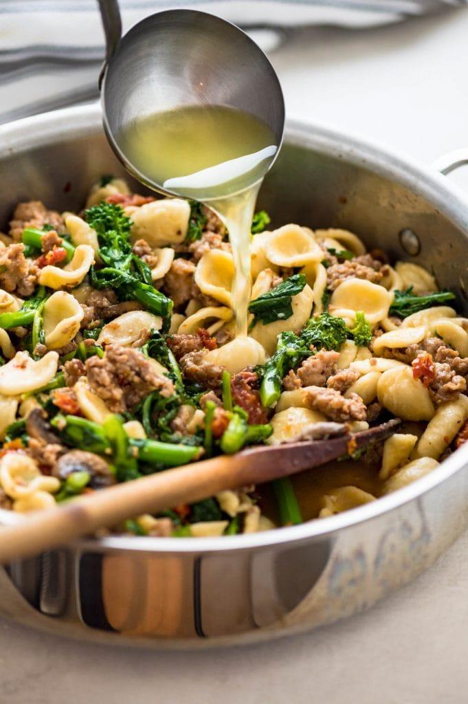 adding pasta water to the orecchiette, sausage and broccoli rabe.