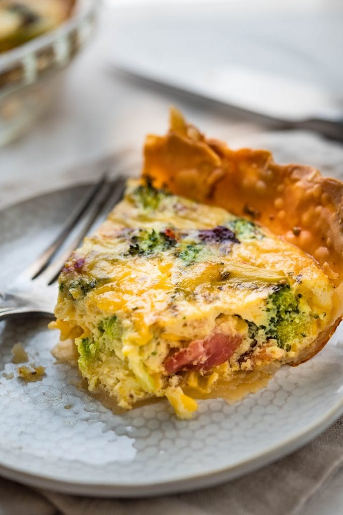 A slice of broccoli cheddar quiche with a bite taken.