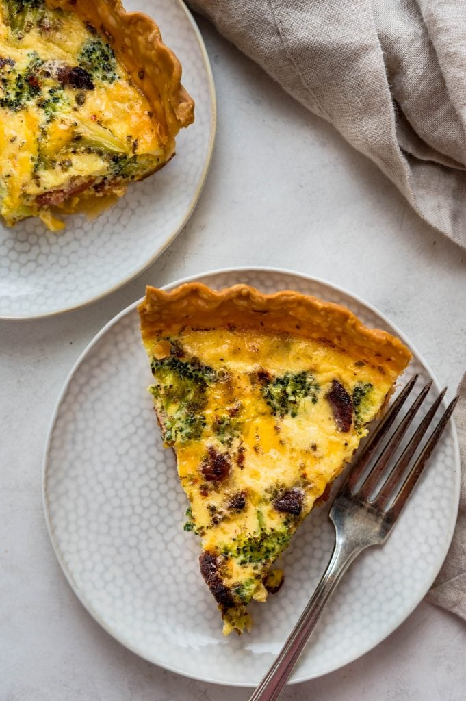 Serving the broccoli bacon quiche on a plate.