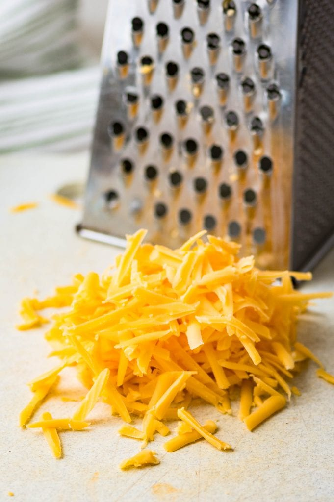 Grating the cheddar cheese for bacon broccoli quiche.