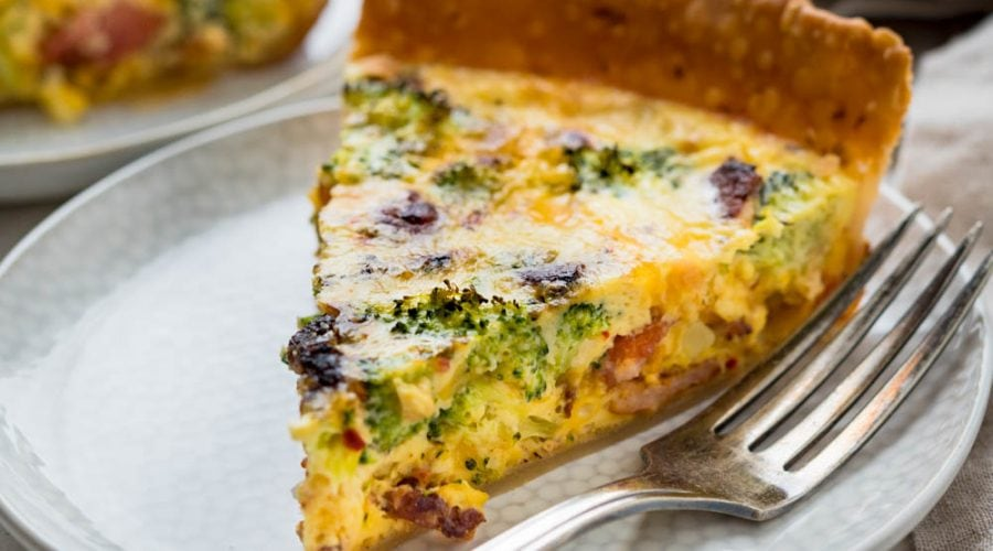 A slice of bacon broccoli quiche on a plate.