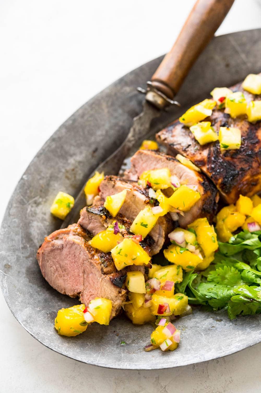 marinated grilled pork tenderloin on a platter with tropical salsa.