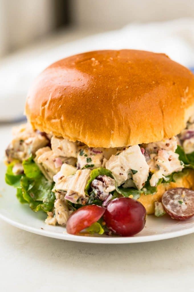 A scoop of homemade chicken salad on a brioche bun.
