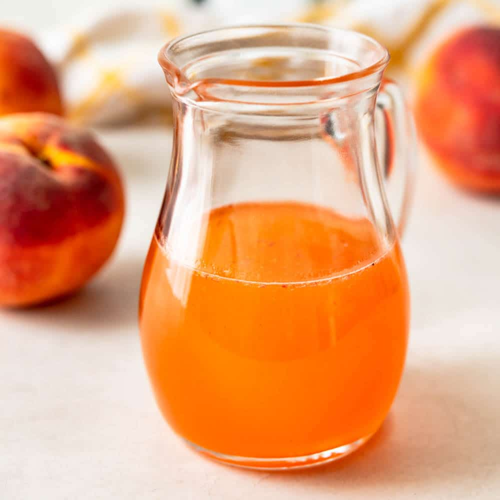 peach simple syrup in a glass pitcher.